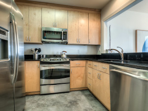 Kitchen with stainless steel appliances, custom cabinetry, and granite countertops